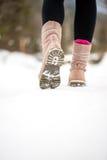 Kvinna som går i väg från kameran till och med vintersnö Arkivfoto
