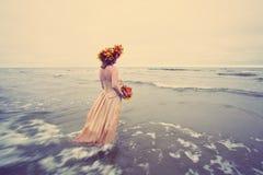 Kvinna som går in i vatten i höst arkivbilder