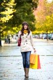 Kvinna som går med shoppingpåsar i höst Arkivbilder