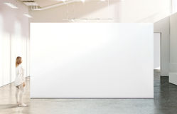 Kvinna som går nära tom vit väggmodell i modernt galleri Royaltyfri Bild