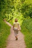 Kvinna som går ner en vandringsled på en solig dag Royaltyfri Fotografi