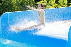 Kvinna som går ner en vattenglidbana Arkivfoto