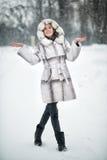 Kvinna som går och har gyckel på den insnöade vinterskogen royaltyfri fotografi