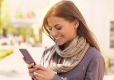 Kvinna som går och smsar på den smarta telefonen i gatan på solig dag för ummer arkivbild