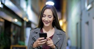 Kvinna som går och smsar på telefonen i natten
