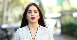 Kvinna som går och talar till kameran i gatan