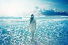 Kvinna som går på den drömlika stranden som tycker om havsikt Royaltyfri Fotografi
