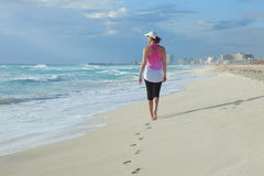 Kvinna som går på en karibisk strand i morgonen Arkivfoton