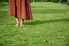 Kvinna som går på gräset Fotografering för Bildbyråer