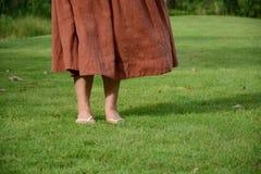 Kvinna som går på gräset Arkivfoto