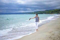 Kvinna som går på stranden Arkivbild