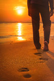 Kvinna som går på stranden på solnedgången som lämnar fotspår Royaltyfri Bild