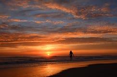 Kvinna som går på stranden på soluppgång royaltyfria foton