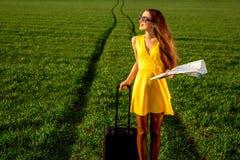 Kvinna som går på vägen i greenfield Arkivbild