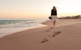 Kvinna som går strandsolnedgång
