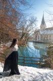Kvinna som går till och med snö på a lakeshore Royaltyfria Bilder