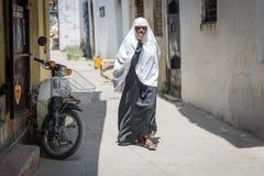 Kvinna som går till och med stenstaden, Zanzibar tanzania royaltyfri foto