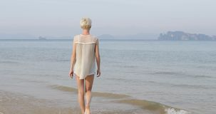 Kvinna som går till vatten på stranden, tillbaka bakre sikt för ung flicka arkivfilmer
