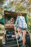 Kvinna som går upp stege till tältet över bilen arkivbild