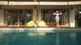 Kvinna som går ut ur villan till simbassängen lager videofilmer