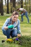 Kvinna som gödslar blommor Arkivbild