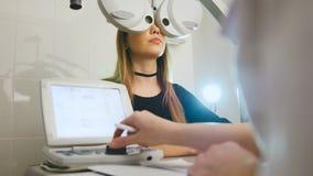 Kvinna som gör ögonprovet med optometrikern i vårdcentral Arkivfoto