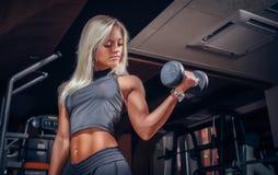 Kvinna som gör övningar med hanteln i idrottshallen Arkivbild