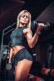 Kvinna som gör övningar med hanteln i idrottshallen Royaltyfri Bild