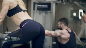 Kvinna som gör övningen för benbakdelar i konditionstudio lager videofilmer