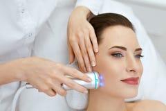 _ Kvinna som gör blå ljus ansikts- behandling på framsidahud royaltyfri fotografi