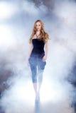 Kvinna som gör catwalken i dimma Fotografering för Bildbyråer