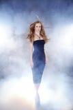 Kvinna som gör catwalken i dimma Arkivfoton