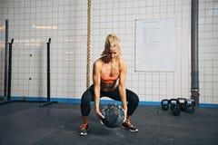 Kvinna som gör crossfitgenomkörare med medicinbollen på idrottshallen Arkivbild