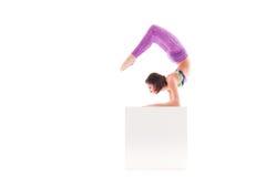 Kvinna som gör det akrobatiska tricket som isoleras på vit Arkivfoto