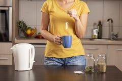 Kvinna som gör en kopp te royaltyfria bilder