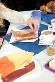 Kvinna som gör en skinka att rulla för frukost Arkivfoton
