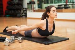 Kvinna som gör en tillbaka krullning på idrottshallen Royaltyfria Foton