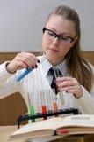 Kvinna som gör experiment i kemi arkivfoton