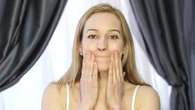 Kvinna som gör framsidakondition som åldras chang i musklerna av framsidan förstärkning av det övre och fäller ned ögonlocket arkivfilmer