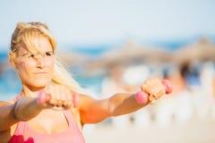 Kvinna som gör genomkörare med hantlar på stranden arkivbild