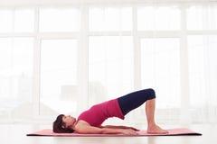 Kvinna som gör gymnastik som bron poserar på en matt rosa yoga Royaltyfri Bild