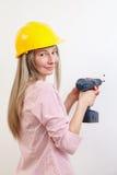 Kvinna som gör hjälmen för arbete och för bära för DIY den skyddande royaltyfri bild