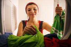 Kvinna som gör hushållning som tar torr kläder från torrare hemmastatt Royaltyfri Fotografi