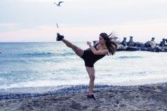 Kvinna som gör kampsporter på stranden Arkivfoton