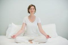 Kvinna som gör meditation på säng i sovrum Royaltyfria Foton