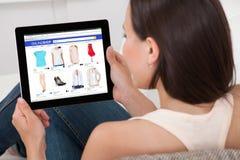 Kvinna som gör online-shopping på den Digital minnestavlan royaltyfria bilder