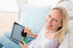 Kvinna som gör online-shopping på den digitala minnestavlan i vardagsrum Arkivbilder