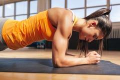 Kvinna som gör press-UPS i idrottshall Royaltyfri Fotografi