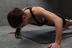 Kvinna som gör push-UPS i idrottshall arkivfoto