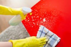 Kvinna som gör ren den röda tabellen med den sprejtvättmedel och trasan Arkivbilder